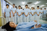 Mizusawa Gakuen School of Nursing: nursing students observing co-students being evaluated during basic hygiene procedure.