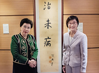 """Day 1: Dr Margaret Chan, WHO Director General (left) and Dr Constance Chan Hon-yee, Director of Health, Department of Health, Hong Kong, Alternate (right) posing in front a calligraphy with the three Chinese words  """"治未病"""". The calligraphy is a gift from Hong Kong Special Administrative Region to the Art Gallery of the WHO Western Pacific Regional Office.   Professor  JaoTsung-I is a distinguished and world- renowned Sinologist."""