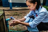 Elementary school student washing her hand.