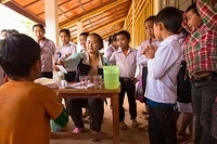 Health workers preparing for the vaccination campaign as the while the villagers are lining up. Nationwide Measles and Rubella Campaign in Lao People's Democratic Republic, 17- 30 November 2014.