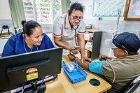 Health workers taking the blood pressure of a patient in Tupapa Community Clinic in Rarotonga.