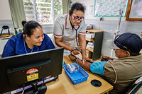 Health workers taking the blood pressure of a patient in Tupapa Community Clinic in Rotatonga.