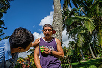 A registered nurse checking the medication of her patient with schizophrenia during her weekly visit at his home in Rarotonga.