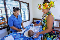 A mother placing her child on a weighing scale at Te Piri Community Clinic in Rarotonga