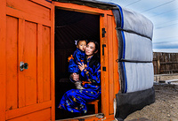 A woman with her daughter in their Ger, a portable  round tent covered with skins, in Darkhan.