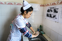A nurse washes her hands before making a routine visit to patients, Khanh Vinh district hospital