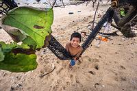 A child in a hammock on the beach in South Tarawa, Kiribati.