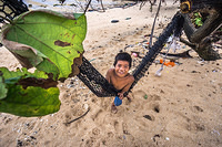 A child in a hammock on the beach in South Tarawa, Kiribati.