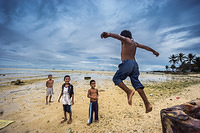 During low tide,  children are playing on a beach in South Tarawa, Kiribati.