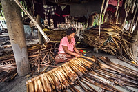 A woman weaves palm leaves that are used for roofing in South Tawara, Kiribati.