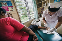 Nurse providing foot care to a woman living with diabetes at the Colonial War Memorial hospital