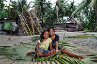 Sisters are weaving palm fronds for roofing