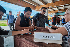 A health inspector checks the arriving passengers in Tuvalu airport.