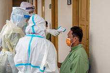 Doctor on duty during room visits  and checking the temperature of a low risk COVID-19 patient
