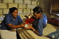 A health care worker provides TB medication during a home visit to a patient