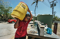 A man carrying gallon of water he fetched from a water distribution center.
