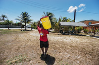 A man carrying a water gallon.