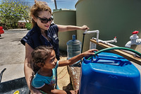 Dr Sevil Huseynova, WHO Representative in Solomon Islands, talking to a girl while fetching water at a water distribution station.