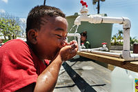 A boy drinking in a water distribution center.
